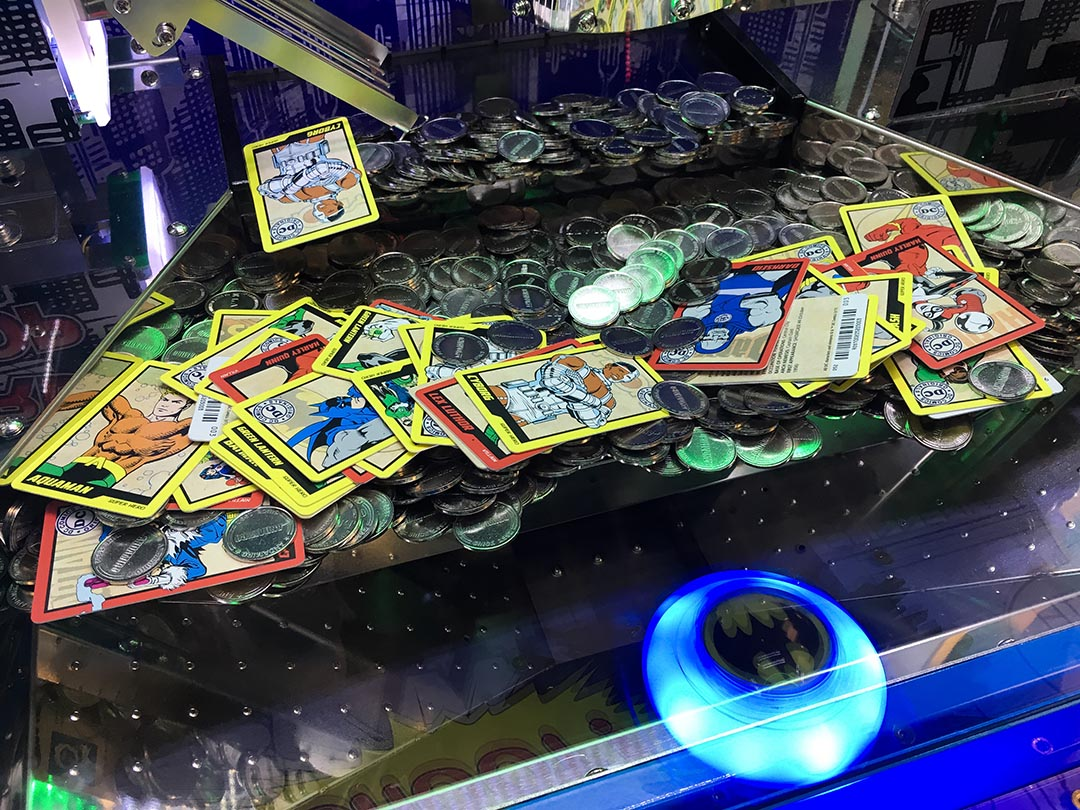 Image of coins and cards available on the DC Comics Super Heroes Coin Pusher Arcade Game